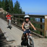 children bicycling on the trestles